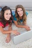 Deux jeunes amis féminins à l'aide de l'ordinateur portable à la maison Image libre de droits