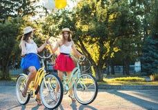Deux jeunes amis féminins élégants sur une bicyclette en parc Meilleurs amis appréciant un jour sur le vélo Images libres de droits
