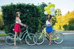 Deux jeunes amis féminins élégants sur une bicyclette en parc Meilleurs amis appréciant un jour sur le vélo Photos libres de droits