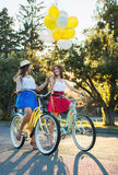 Deux jeunes amis féminins élégants sur une bicyclette en parc Meilleurs amis appréciant un jour sur le vélo Photo libre de droits