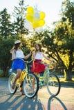 Deux jeunes amis féminins élégants sur une bicyclette en parc Meilleurs amis appréciant un jour sur le vélo Images stock