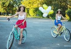 Deux jeunes amis féminins élégants sur une bicyclette en parc Meilleurs amis appréciant un jour sur le vélo Image stock