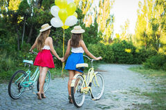 Deux jeunes amis féminins élégants sur une bicyclette en parc Meilleurs amis appréciant un jour sur le vélo Photos stock
