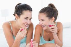 Deux jeunes amis féminins appliquant le maquillage dans le lit Image libre de droits