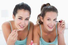 Deux jeunes amis féminins appliquant le maquillage dans le lit Image stock