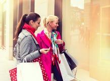 Deux jeunes amis féminins attirants appréciant un jour faisant des emplettes, image colorised Photos stock