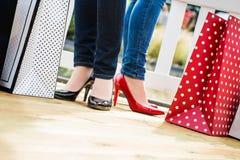 Deux jeunes amis féminins attirants appréciant une coupure après des achats de succesfull Photographie stock libre de droits