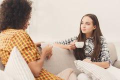 Deux jeunes amis féminins avec du café conversant Photos libres de droits