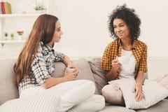 Deux jeunes amis féminins avec du café conversant Image libre de droits
