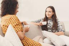 Deux jeunes amis féminins avec du café conversant Photo libre de droits