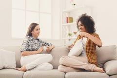 Deux jeunes amis féminins avec du café conversant Photographie stock