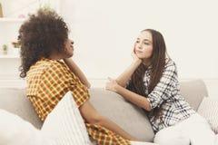 Deux jeunes amis féminins avec du café conversant Image stock