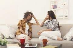 Deux jeunes amis féminins avec du café conversant Images libres de droits