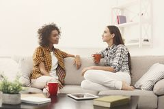 Deux jeunes amis féminins avec du café conversant Photos stock