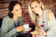 Deux jeunes amis féminins bavardant dans une barre Images stock