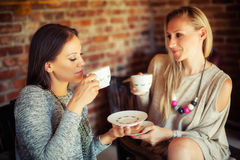 Deux jeunes amis féminins bavardant dans une barre Photo stock