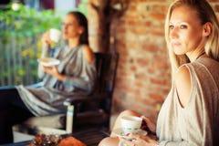 Deux jeunes amis féminins bavardant dans une barre Image stock