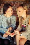 Deux jeunes amis féminins bavardant dans une barre Photos stock