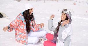 Deux jeunes amis féminins causant dans la neige Photographie stock libre de droits