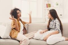 Deux jeunes amis féminins conversant à la maison Image stock
