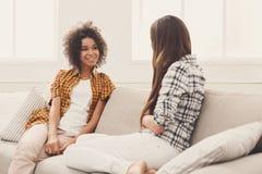 Deux jeunes amis féminins conversant à la maison Photos stock