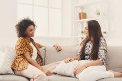 Deux jeunes amis féminins conversant à la maison Image libre de droits
