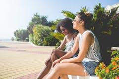 Deux jeunes amis féminins détendant dehors au soleil Images libres de droits