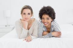 Deux jeunes amis féminins de sourire se situant dans le lit Photo libre de droits