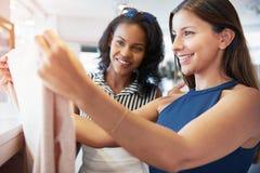 Deux jeunes amis féminins faisant des emplettes pour des vêtements Images stock