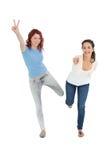 Deux jeunes amis féminins gais avec des gestes de main Image stock