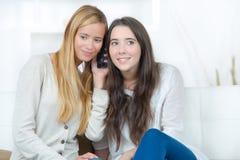 Deux jeunes amis féminins heureux écoutant la conversation Image libre de droits