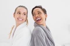 Deux jeunes amis féminins heureux dans des peignoirs Image stock