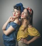 Deux jeunes amis féminins heureux dans le rétro habillement Photo stock