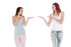 Deux jeunes amis féminins heureux donnant leurs mains Photo stock