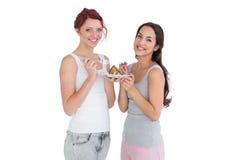 Deux jeunes amis féminins heureux mangeant de la pâtisserie ensemble Image libre de droits