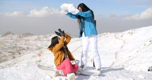 Deux jeunes amis féminins jouant dans la neige Photos libres de droits