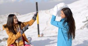 Deux jeunes amis féminins jouant dans la neige Images stock