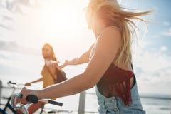 Deux jeunes amis féminins montant leurs bicyclettes Images stock