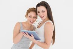 Deux jeunes amis féminins occasionnels avec le comprimé numérique Image libre de droits