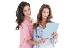 Deux jeunes amis féminins occasionnels avec le comprimé numérique Photo libre de droits