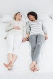 Deux jeunes amis féminins occasionnels se situant dans le lit Image stock