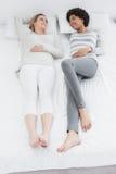 Deux jeunes amis féminins occasionnels se situant dans le lit Photos libres de droits
