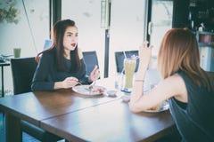 Deux jeunes amis féminins rient et prenant le déjeuner ensemble au repos Photographie stock libre de droits
