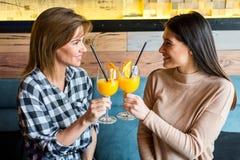 Deux jeunes amis féminins s'asseyant dans le café, le café potable et le ju Photo stock