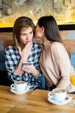 Deux jeunes amis féminins s'asseyant dans le café, le café potable et le ju Image stock