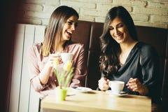 Deux jeunes amis féminins s'asseyant dans un café et un café de boissons Photographie stock