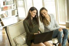 Deux jeunes amis féminins s'asseyant dans une chambre Photos stock