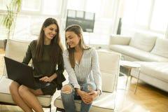 Deux jeunes amis féminins s'asseyant dans une chambre Images stock