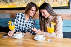 Deux jeunes amis féminins s'asseyant en café Image stock