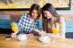 Deux jeunes amis féminins s'asseyant en café Photo libre de droits